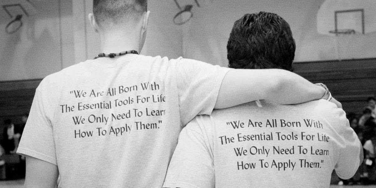 "Backs of 2 coaches with T-shirts reading ""We are all born with the essential tools for life. We only need to learn how to apply them."""